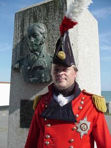 Sir John Moore re-enactor standing next to Sir John Moore memorial